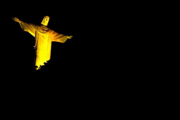 O monumento do Cristo Redentor iluminado na cor amarela por doação de medula óssea